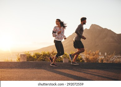 Young couple jogging early in morning, with woman looking back over her shoulder. Young man and woman running outdoors on a country road.