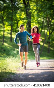 Young couple jogging at the park.Green environment.