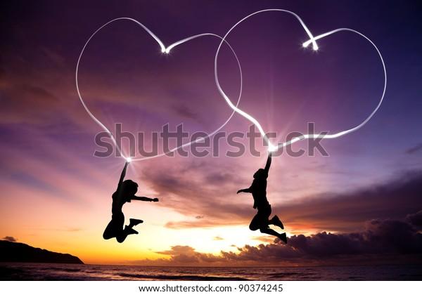 日の出前に海岸の空中を懐中電灯で飛び跳ね、つながった心を描く若い夫婦