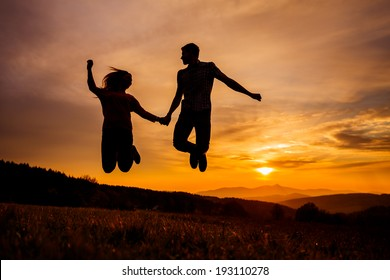Young Couple Jumping During Sunset, Beautiful Romantic Background, People in Love Silhouettes