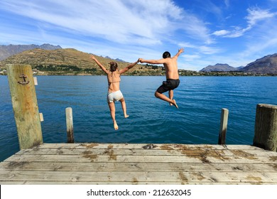 Young couple jumping on the edge of a dock into the Lake Wakatipu