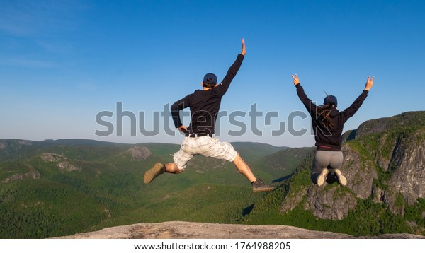 young-couple-jumping-summit-la-600w-1764