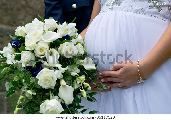 A young couple just married carrying their first child.