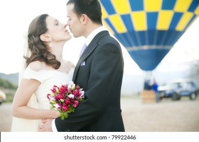 Young couple just married in a hot air balloon (focus on bouquet)