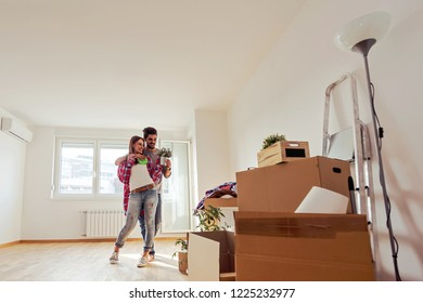 Young couple just moved into new empty apartment unpacking and cleaning - relocation