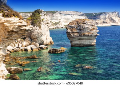 Young couple kayaking near Bonifacio town on beautiful white rock cliff with sea bay, Corsica, France, Europe.