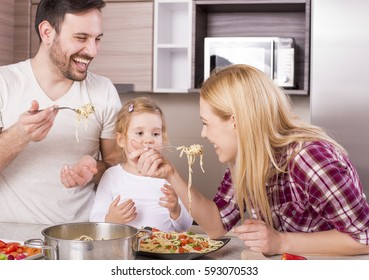 Young couple with kid having fun in the kitchen while preparing spaghetti and vegetable salad