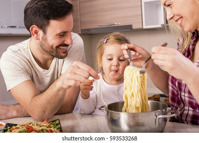 Young couple with kid having fun in the kitchen while preparing spaghetti