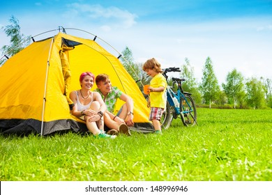Young couple with kid sitting in the tent on a bike hiking trip