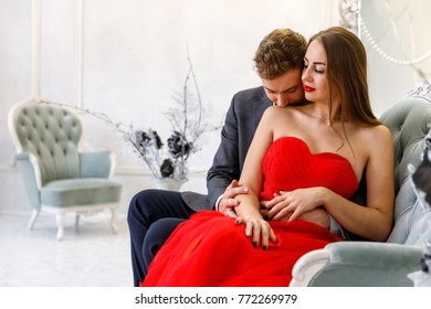 Young couple kiss. Man and woman in evening outfits on the sofa in the white room