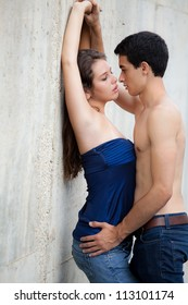 Young Couple Kissing Against Wall