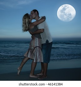 Young couple kissing at the beach under moonlight