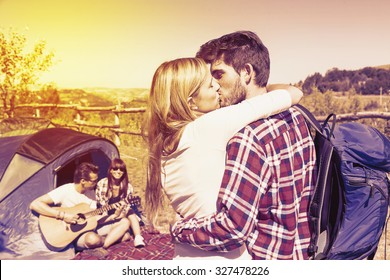 young couple kissing in a camping of the hill on a vintage color filtered look