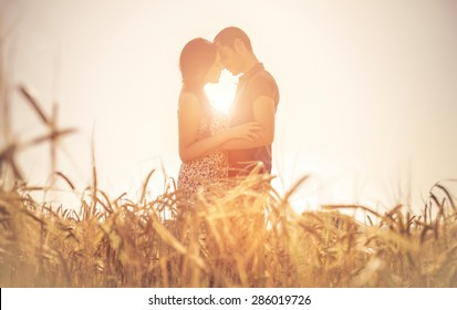 young couple kissing in a field. asian woman hugging a caucasian man in the middle of a wheat field and kissing each other. concept about passion and love