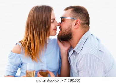 young couple kissing and holding glasses in hands, happy couple enjoying picnic on the beach and have good time on summer vacations