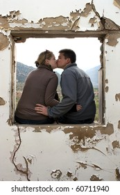 a Young couple kissing inside a window frame of an old building