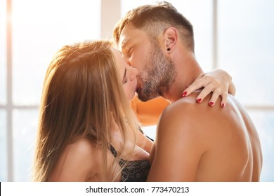 Young couple kissing. Lovers, morning light.