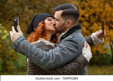 Young couple kissing and making selfie. Problem of people's communication.Internet addiction