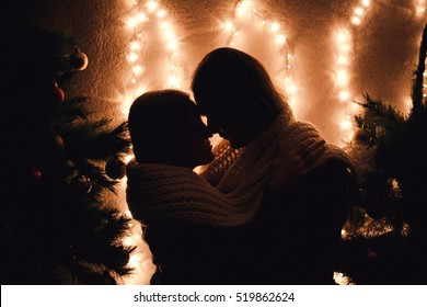 Young couple kissing near Christmas tree. Low key. Silhouette