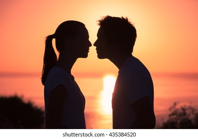 Young couple kissing on the beach during sunset.