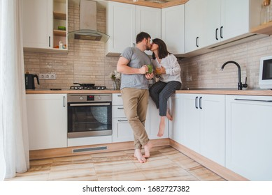 young couple kissing on kitchen while drinking tea