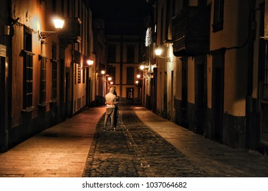 Young couple kissing on the narrow street of the old town of Las Palmas, capital city of gran canaria. Night shoot, with soft romantic scenery lighting.