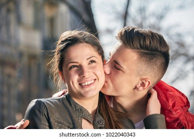 young couple kissing on the street in spring