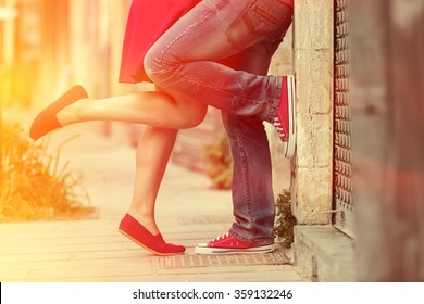 Young couple kissing outdoor. Male and female legs. Cross processed image for vintage look
