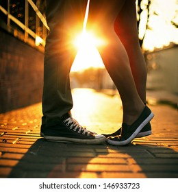 Young couple kissing outdoor in summer sun light. Kiss love date color evening teen.