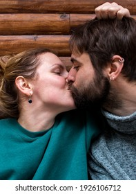 young couple kissing sitting near a wooden house in the forest. attitude and affection for each other. love.