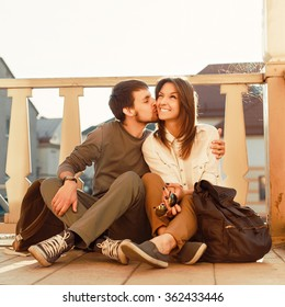 Young couple kissing and smiling outdoor on the street in summer happy lifestyle travel portrait with backpacks