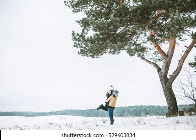 Young couple kissing under a huge pine in a field covered with white snow