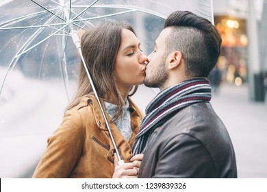 Young couple kissing under umbrella in rainy day in the city center - Romantic lover having a tender moment outdoor - People, love and relationship concept