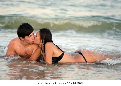 Young couple kissing while lying in waves