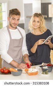 Young couple in kitchen cooking dinner together