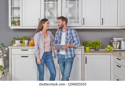 Young couple in the kitchen with digital tablet