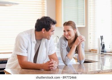 Young couple in the kitchen looking at each other