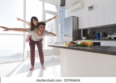 Young Couple In Kitchen, Lovers Hispanic Man Carry Asian Woman Modern Apartment With Big Windows Interior
