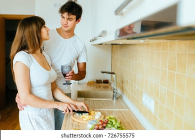 Young couple in kitchen in the morning, hispanic woman and european man hug drink tea and cooking breakfast in modern apartment interior. Real people concept.