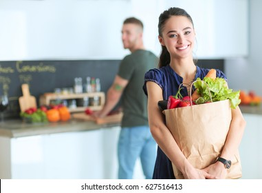 Young couple in the kitchen , woman with a bag of groceries shopping
