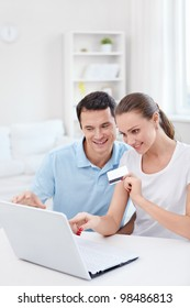 Young couple with laptop and credit card at home
