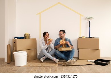 Young couple laughing while sitting on the ground making a break from moving-in and holding slice of pizza in their hands.