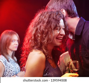 Young couple laughing and whispering while Woman in the backround is looking at them jealously, in night club, focus on couple.