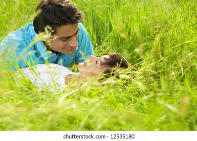 young couple laying down in meadow and hugging