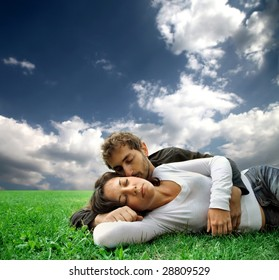 young couple laying in a grass field