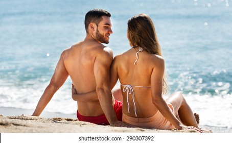 Young couple laying on sandy beach at sea shore in sunny day