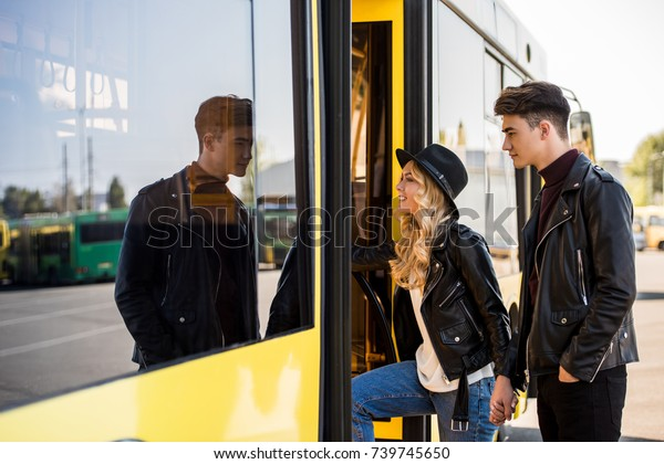 young couple in leather jackets holding hands and entering public transport