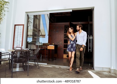 Young couple leaving satisfied from restaurant
