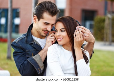 Young couple listening music by headphones outdoor in park