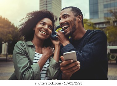Young couple listening music on one headphone